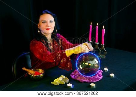 A Young Clairvoyant And Fortuneteller Reads The Future On A Mirror Ball In A Magic Salon On A Black