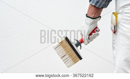 Caucasian House Painter Worker In White Work Overalls And With Protective Gloves, He Holds The Brush