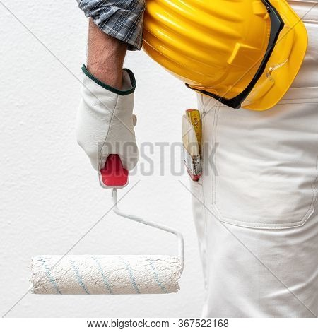 Caucasian House Painter Worker In White Work Overalls And With Protective Gloves, He Holds The Rolle