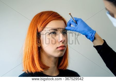 Young Beautician Caucasian Girl Holds Model Eyebrow Correction. Beautician At Work Is The Workplace