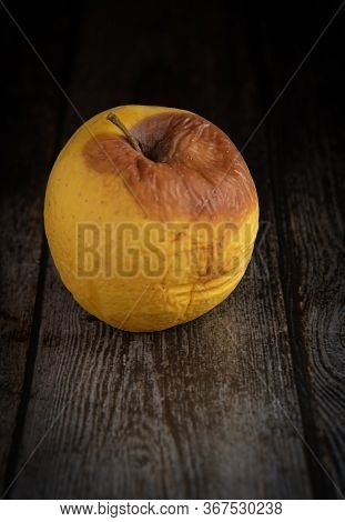 Yellow Wilted Rotten Apple On A Wooden Brown Surface Background