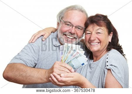 Laughing senior couple with euro notes in their hands