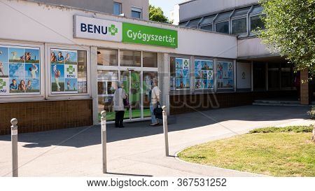 Gyor Hungary 05 21 2020: Elderly Female Customers Are Waiting At The Entrance Of A Benu Pharmacy In