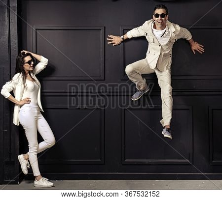 A young cheerful couple wearing sunglasses posing over black background