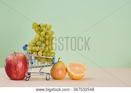 Mellow Bunch Of Grape In Shopping Cart. Apple Lemon And Pear On Table. Summer Healthy Fruit. Copy Sp