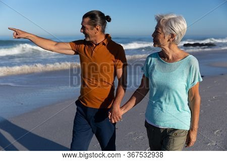 Senior Caucasian couple enjoying time at the beach, walking and holding hands, a man is pointing at the sea