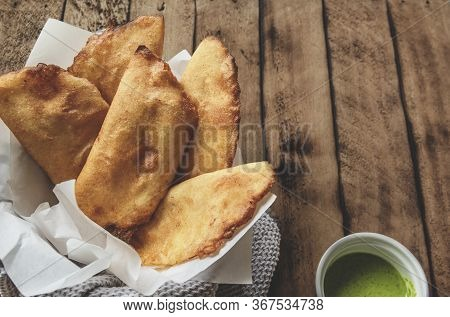 VENEZUELAN COLOMBIAN FOOD. Venezuelan typicals corn empanadas with meat in clay bowl with avocado sa