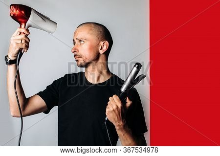 A Bald Brutal Man, Holding A Hair Dryer And Curling Tongs In His Hand, Dries His Hair And Baldness .