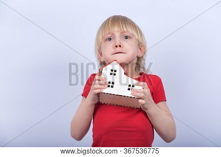 Child With A Troubled Face Holds A Model Of A House. Shelter, Orphan, Adoption.