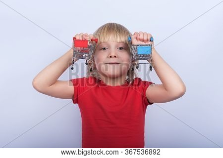 Portrait Of Fair-haired Boy With Toy Shopping Cart On White Background. Concept Of Shopping For Kids