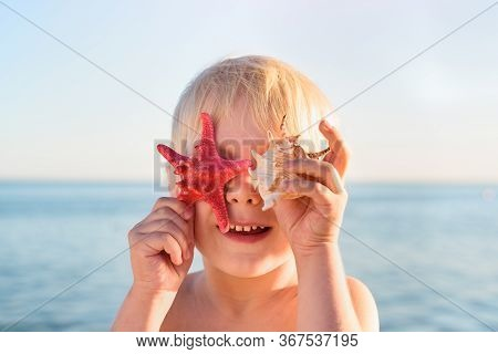Little Fair Hair Boy Playing With Seastar And Shell On Sea Background
