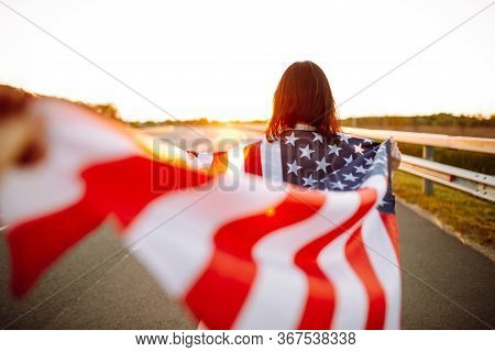 Woman Holding Usa Flag. Independance Day In America. 4th July. Girl Walking Along Highway With Wavin