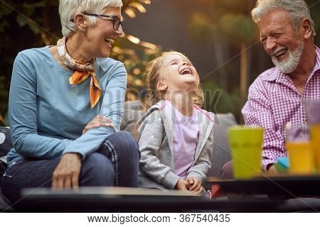 Happy  granddaughter laughing  with her  grandparents.Happy childhood,family and relationships concept.