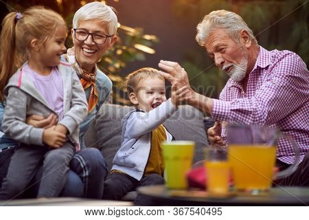 Cheerful grandchildren spending good and funny time with their  happy grandparents.