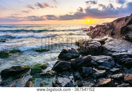 Coast Of The Ocean At Sunset. Beautiful Landscape With Rocks In The Water. Gorgeous Cloudscape Above
