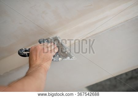 Putty knife in male hand. Hand work? Worker putsty plasterboard ceiling in new appartment. Repairman works with plasterboard, plastering dry-stone wall, home improvement. Man makes repairs at house.
