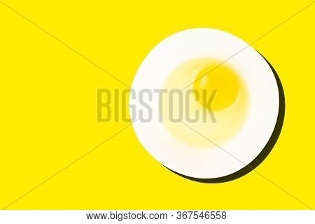 Raw Egg In Bowl With Dark Shadow Isolated On Yellow Background. Healthy Food And Cooking At Home Con