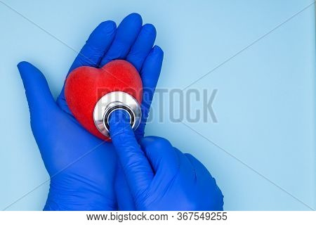 Doctor Cardiologist Hands With Heart In Hands On Blue Background. Concept Of Cardiology And Cardiova