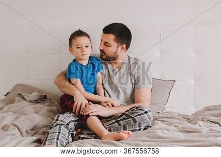 Caucasian Father Talking To Boy Son. Man Parent Hugs Kid Child On Bed In Bedroom At Home. Authentic