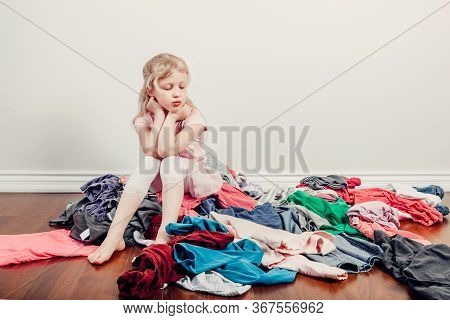 Mommy Little Helper. Bored Caucasian Girl Sorting Clothes. Tired Funny Child Arranging Organazing Cl