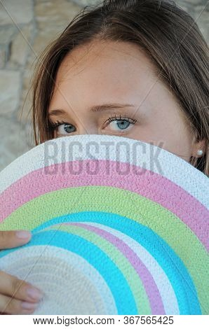 Vertical Portrait Of A Brunette Covering Half Of Her Face With A Straw Hat And Looking At The Camera