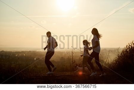 Young And Happy Family - Man, Woman And Girl Are Jogging With Their Dog Outside The City, On The Vil
