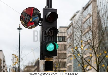 London, England, Uk, Green Traffic Light Signal And Traffic Convex Mirror With The Reflection Of The