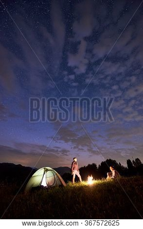 Friends Around A Campfire Near Tent Against Background Powerful Mountains Under A Starry Sky. Nights