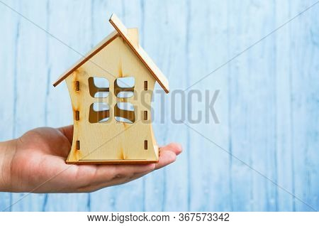Close-up Of A Hand Holding A Model Of A Wooden House On A Blue Background