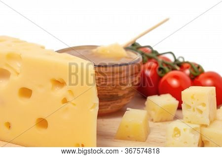 Yellow Maasdam Cheese, Triangular Piece Cheese With Holes, Saucer With Honey, Tomato Wooden Isolated