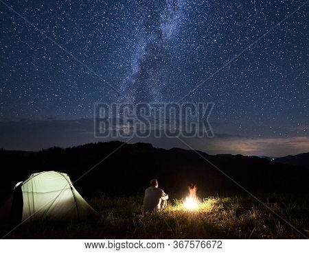 Tourist Is Relaxing Near Bonfire Enjoying The Silhouettes Of Mountains Under Starry Sky With Bright