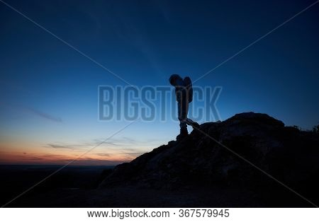Beautiful View Of Space Traveler On Rocky Mountain With Majestic Night Sky On Background. Silhouette