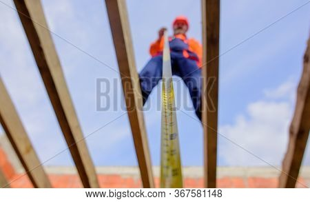 Builder With Tape Measure. Selective Focus. Construction Worker On Construction Site With Roulette.
