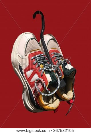 White Platform Sneakers With Bright Color Accents On A Hanger Pattern On Dark Red Background. High P