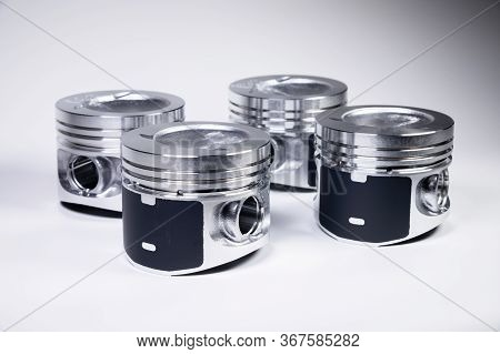 Close-up Of Four New Internal Combustion Engine Piston On A Gray Gradient Background. The Concept Of