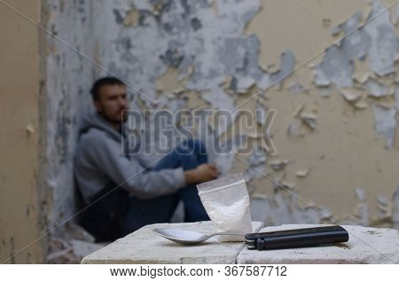 A Drug-dependent Man Suffers From Drug Withdrawal While Sitting In Abandoned Building Next To Dose F