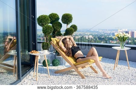 Slender Brunette In Black Bathing Suit Is Basking At Sun On Terrace Apartment With Panoramic View Of