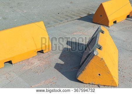 Concrete Anti-terrorism Barriers On A Sidewalk Alongside An Asphalt Street With One Lying On Its Sid
