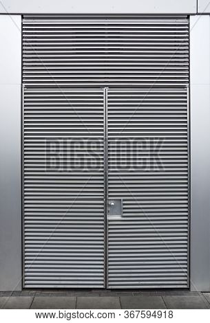 Closed Metallic Grey Double Door With Horizontal Ripples, Viewed From Outside The Building. Full Fra