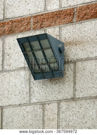 Wall-mounted Black Metal Spotlight For Security And Illumination On An Old Stone Block Wall In A Bot