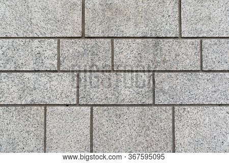 Grey Granite Brick Wall Background Texture With Different Sized Rectangular Blocks In A Full Frame B