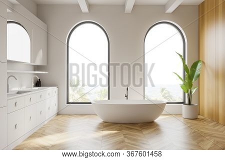 Interior Of Stylish Bathroom With White And Wooden Walls, Wooden Floor, Arched Windows With Blurry T