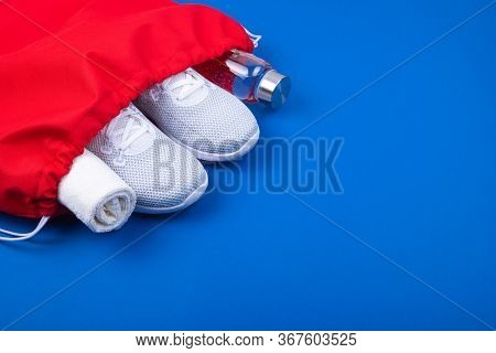 Top View Of White Sport Shoes Sneakers, Reusable Glass Water Bottle And Towel In Red Sport Bag On Cl