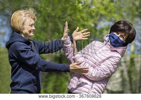 Two Women Outdoors, One In Protective Mask On Face Do Not Want To Hug Another One Without Mask, Tryi