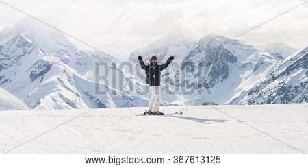 Happy Female Skier On Top Of Mountain Raise Up Hand