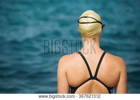 A Swimmer Stands On The Shore Of The Ocean Concentrated For A Competition