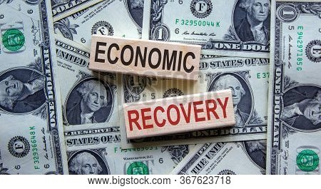 Concept Words 'economic Recovery' On Wooden Blocks On A Beautiful Background From Dollar Bills.
