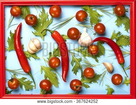 Red Chili Peppers, Garlic, Tomatoes And Green Rucola Salad Leaves Background.