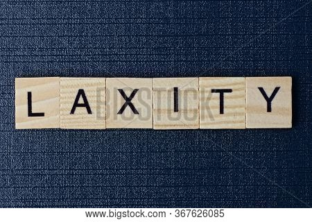 Text On Word Laxity From Gray Wooden Letters On A Black Table