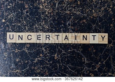 Gray Word Uncertainty From Wooden Letters In Black Font On A Brown Shabby Wall With A Pattern